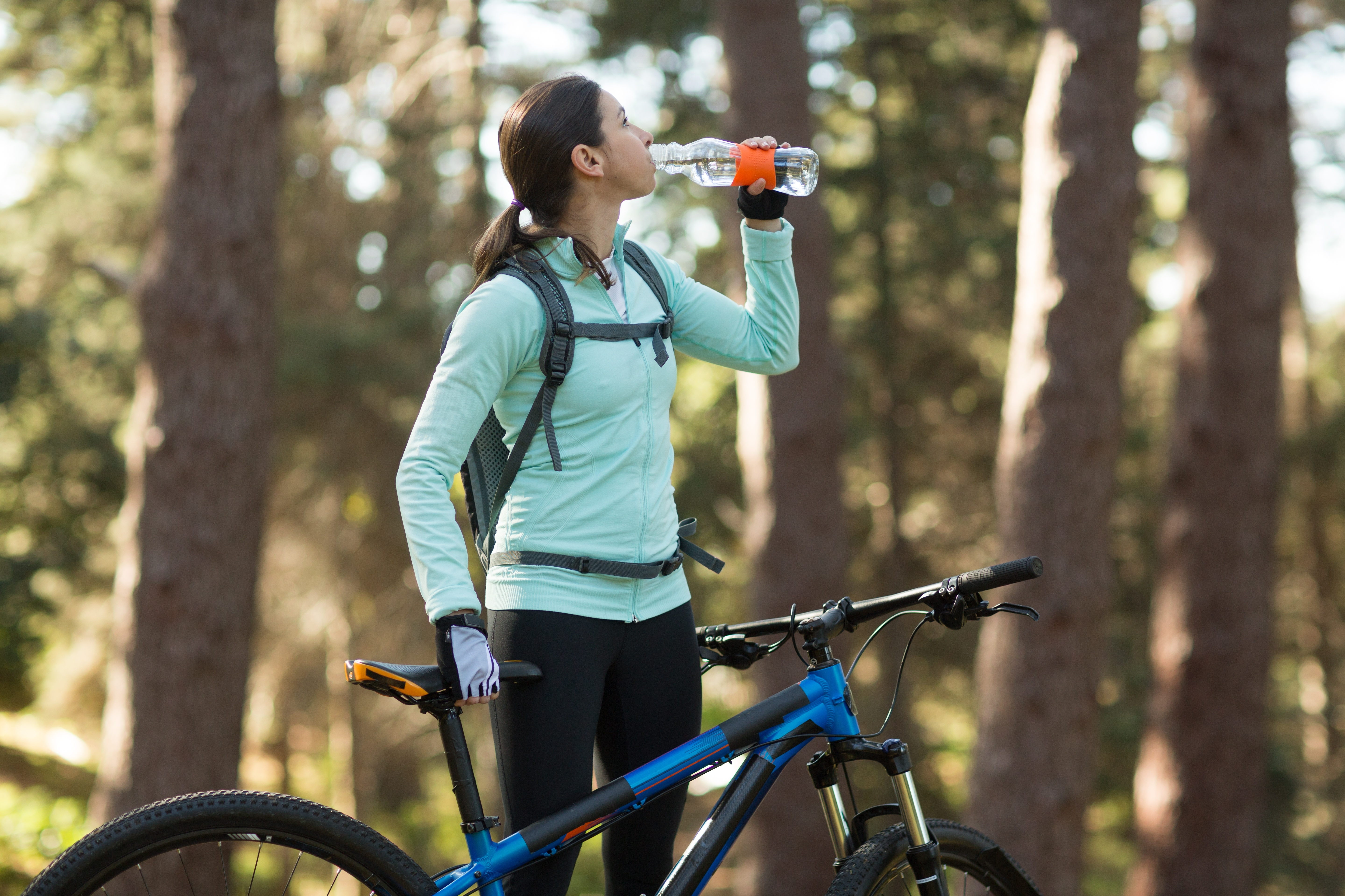 woman hydrating while riding her bike