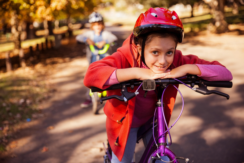 girl in helmet leaning on her bike in a park
