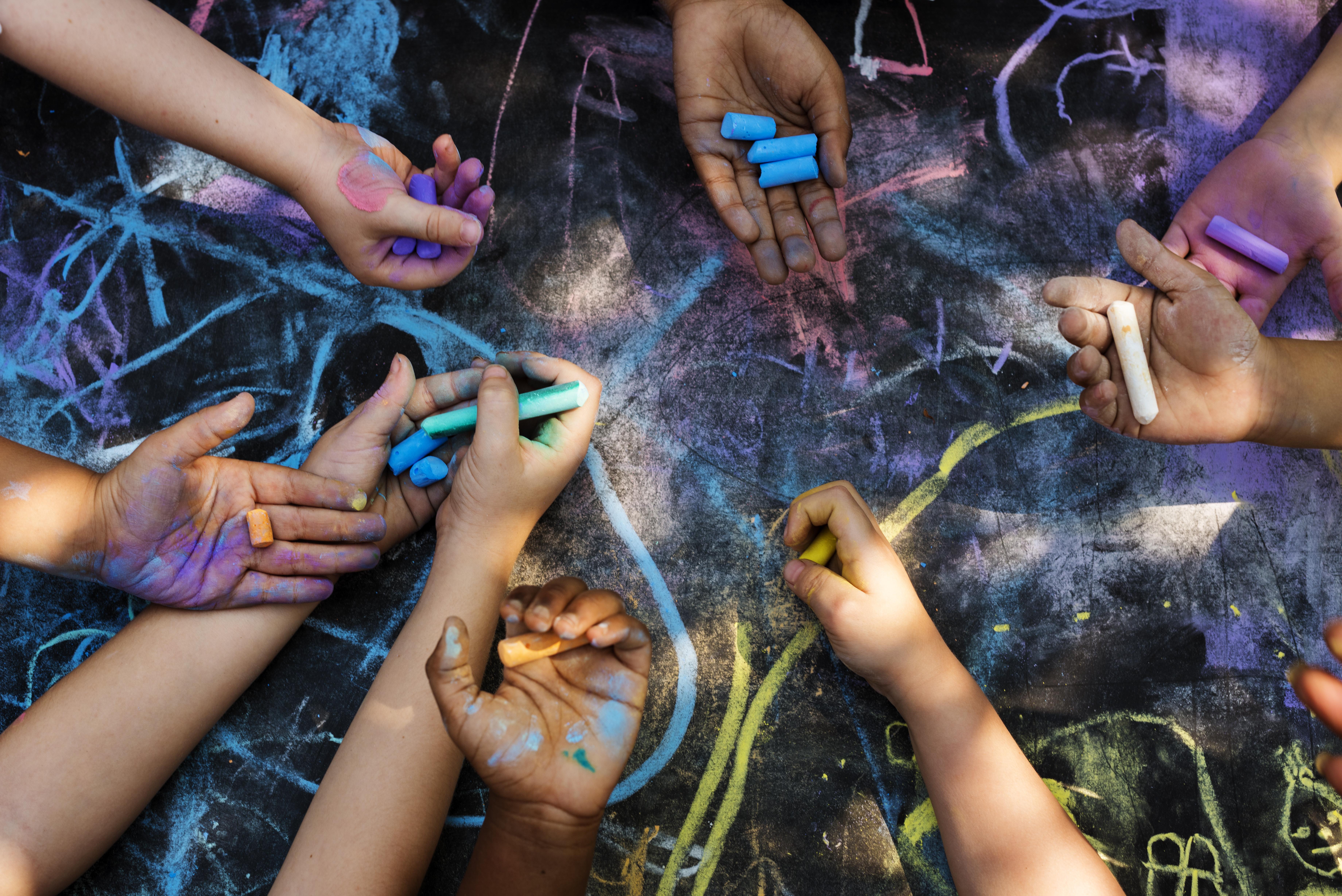 children's hands hold chalk