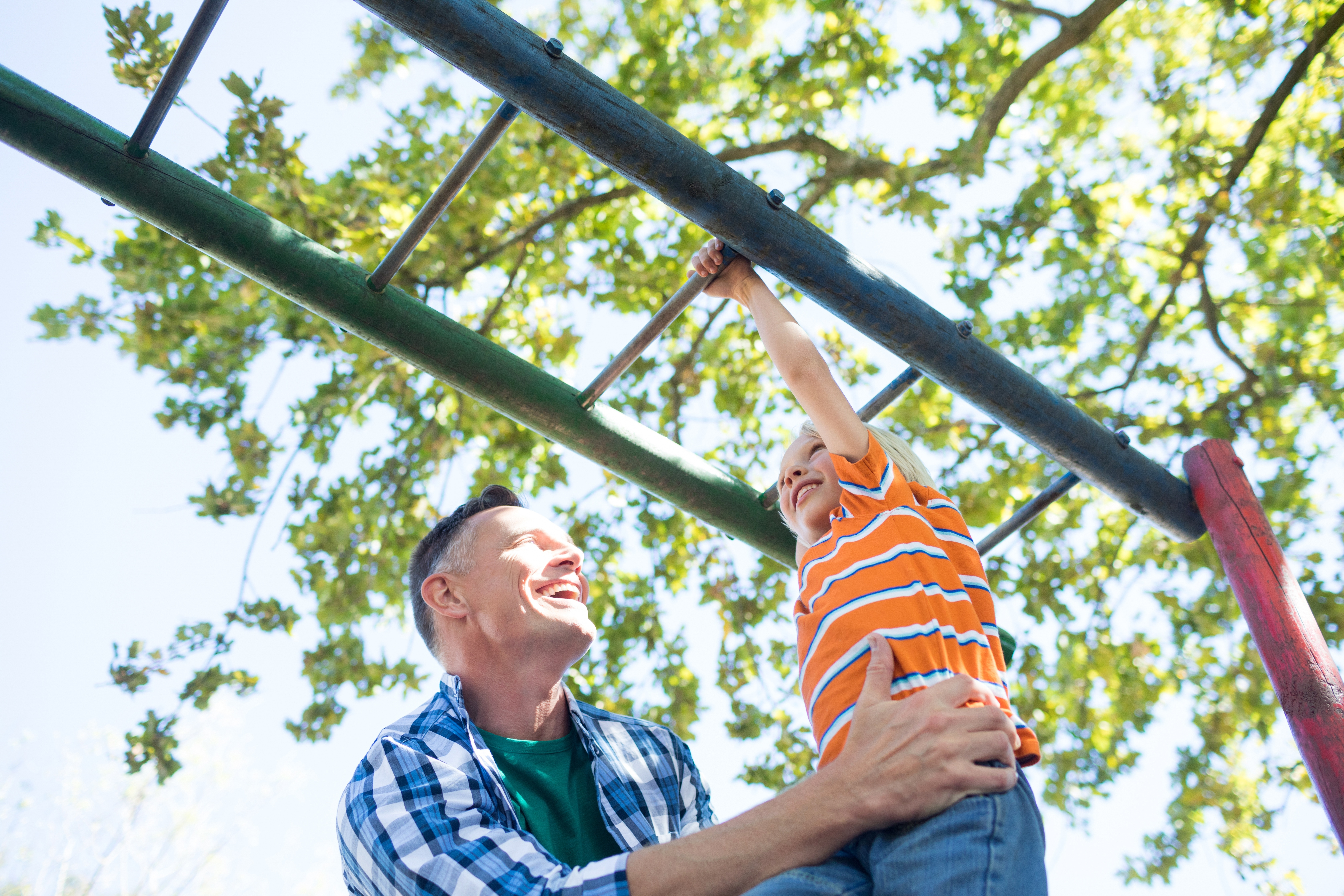 parent helping a child on the monkey bars