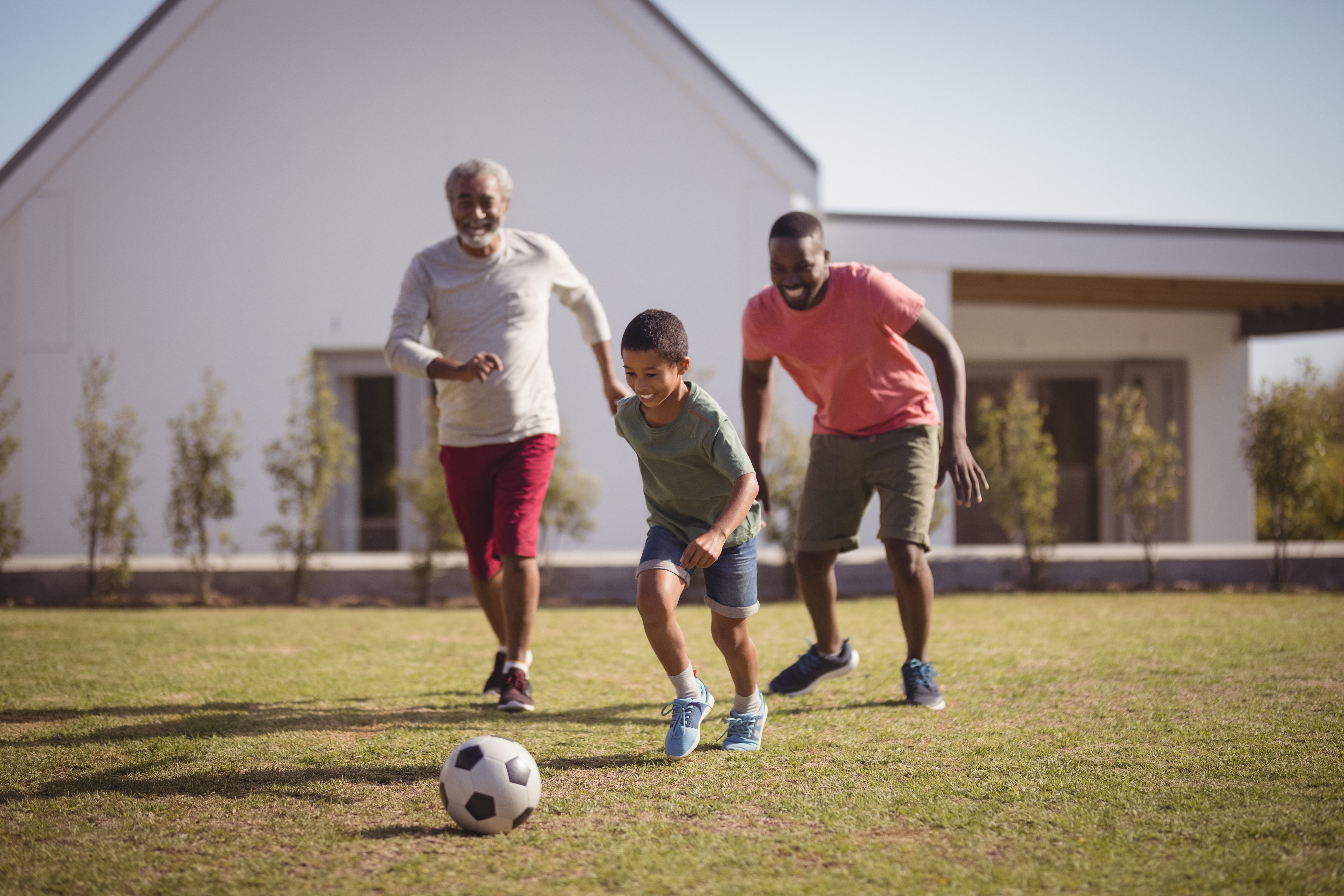 father, son, and grandfather playing soccer