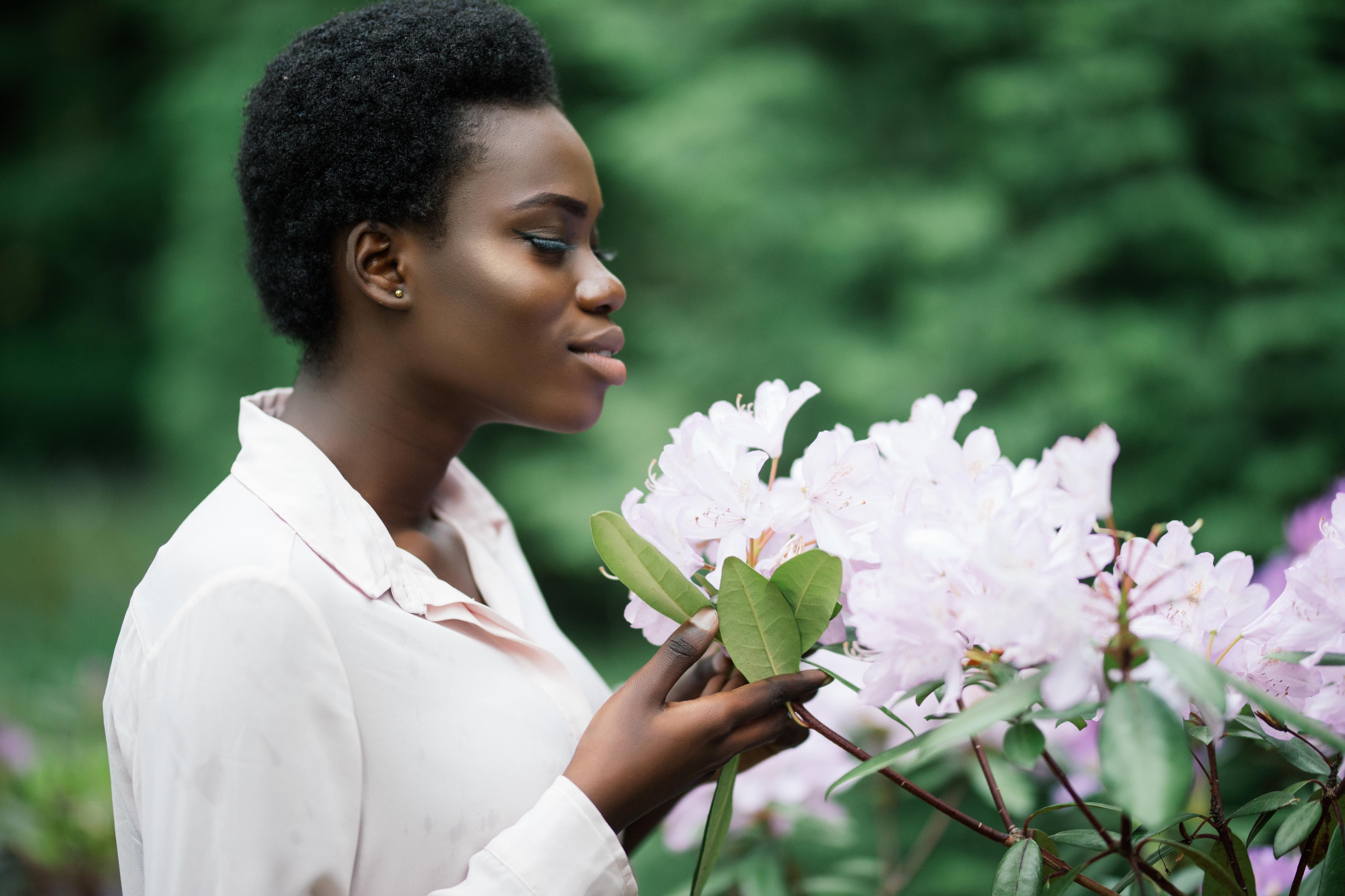 woman examining a flower