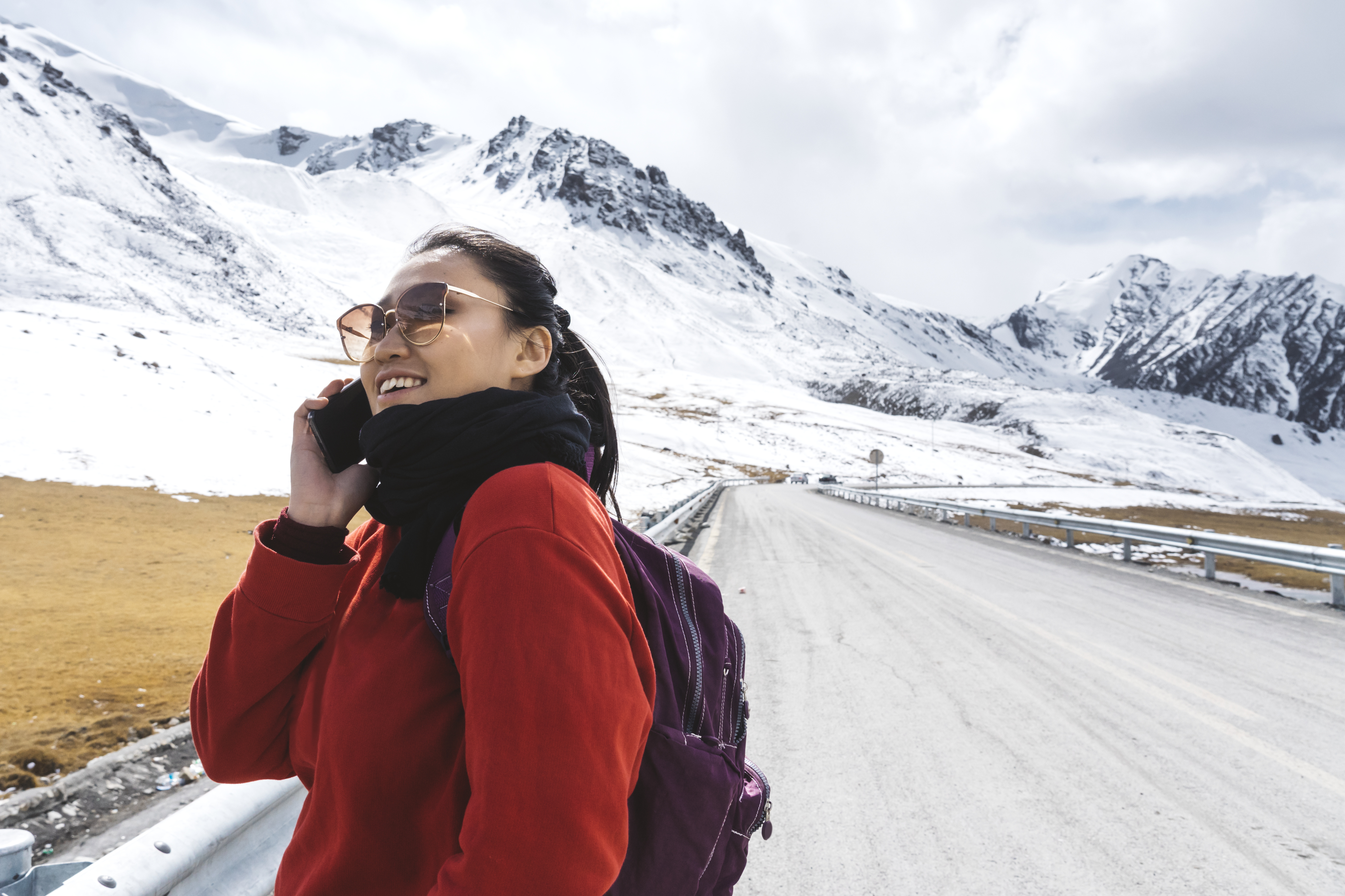 woman on cell phone in front of a mountain