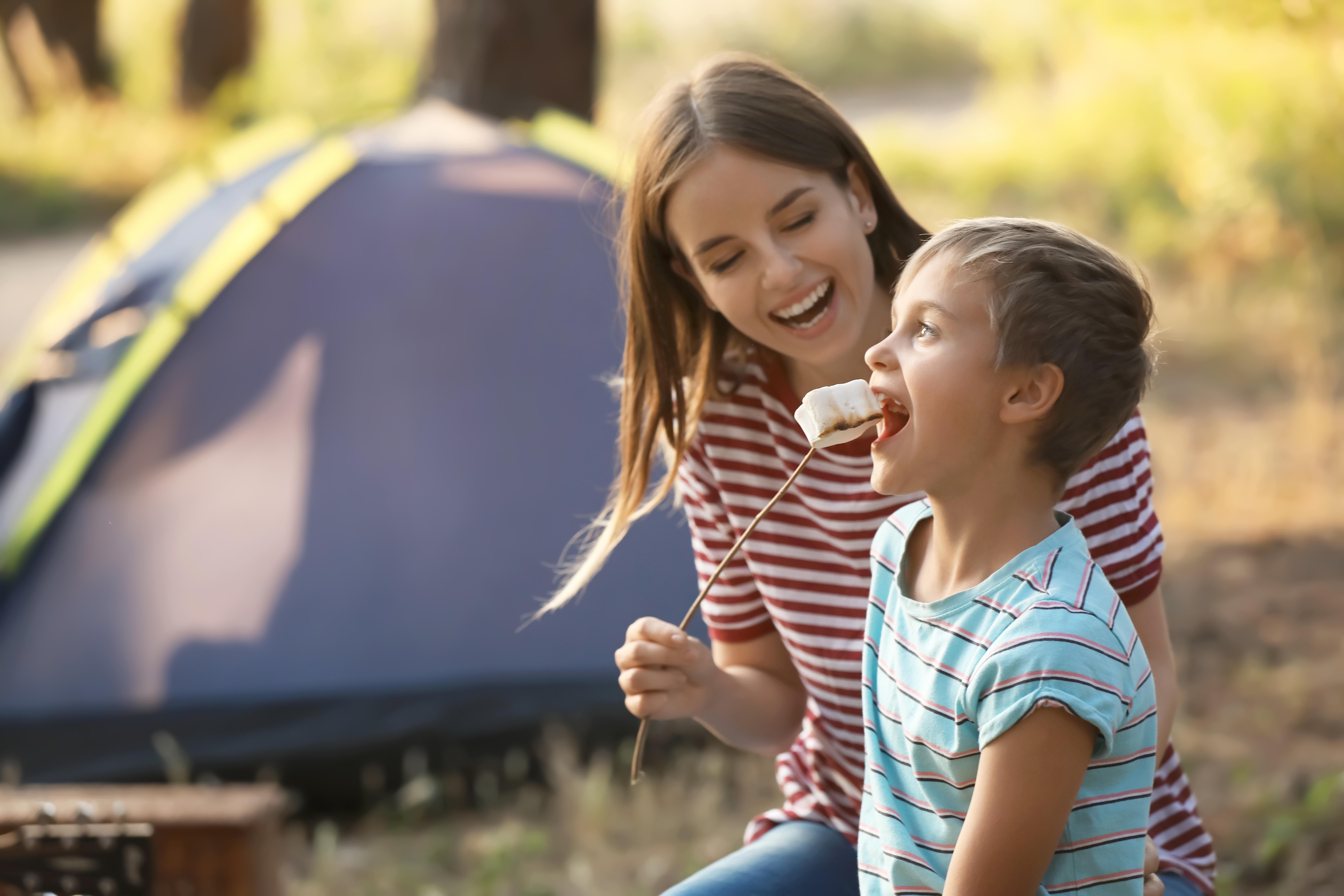 kids eating marshmallows at a campfire
