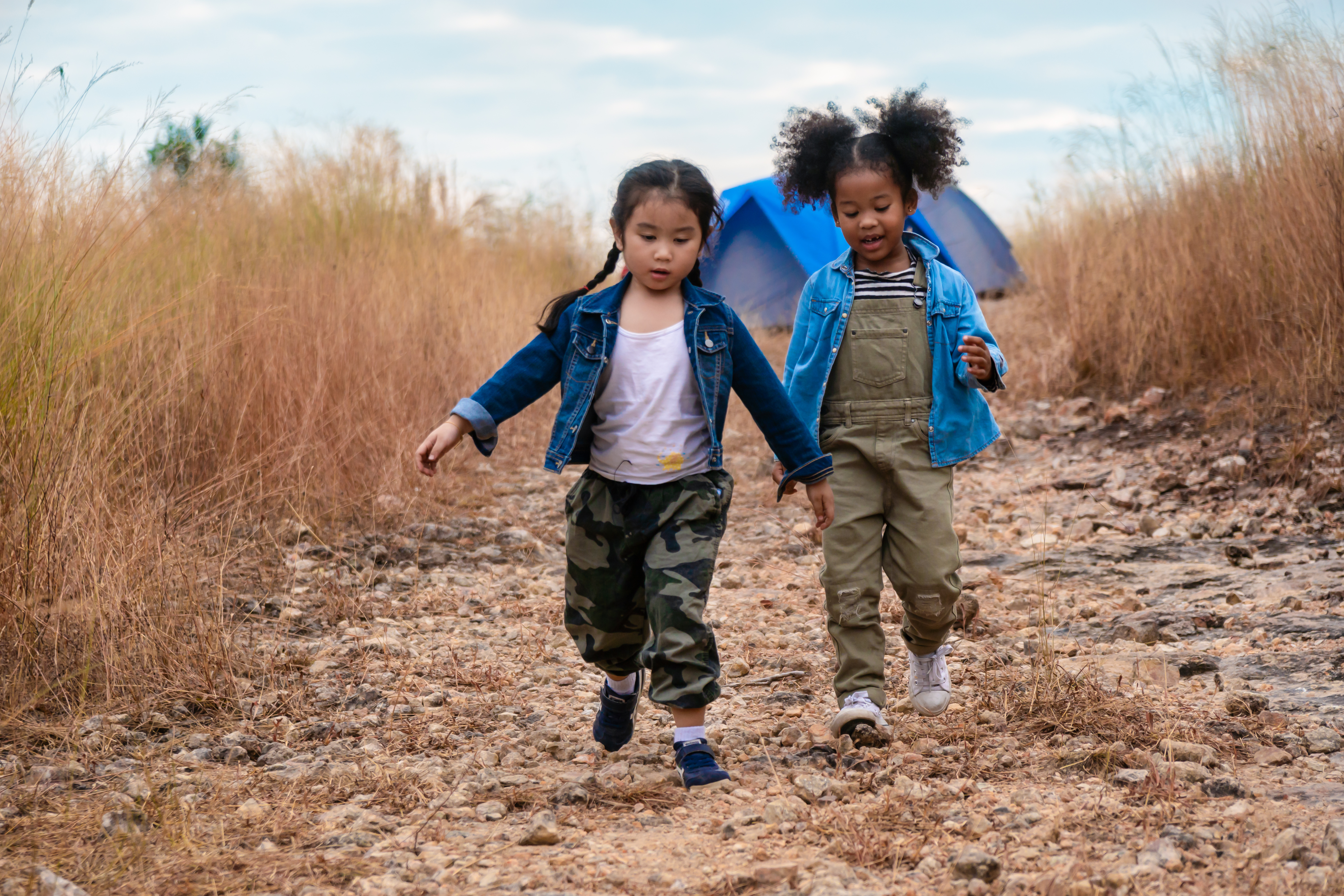 young girls walk near a tent in a field