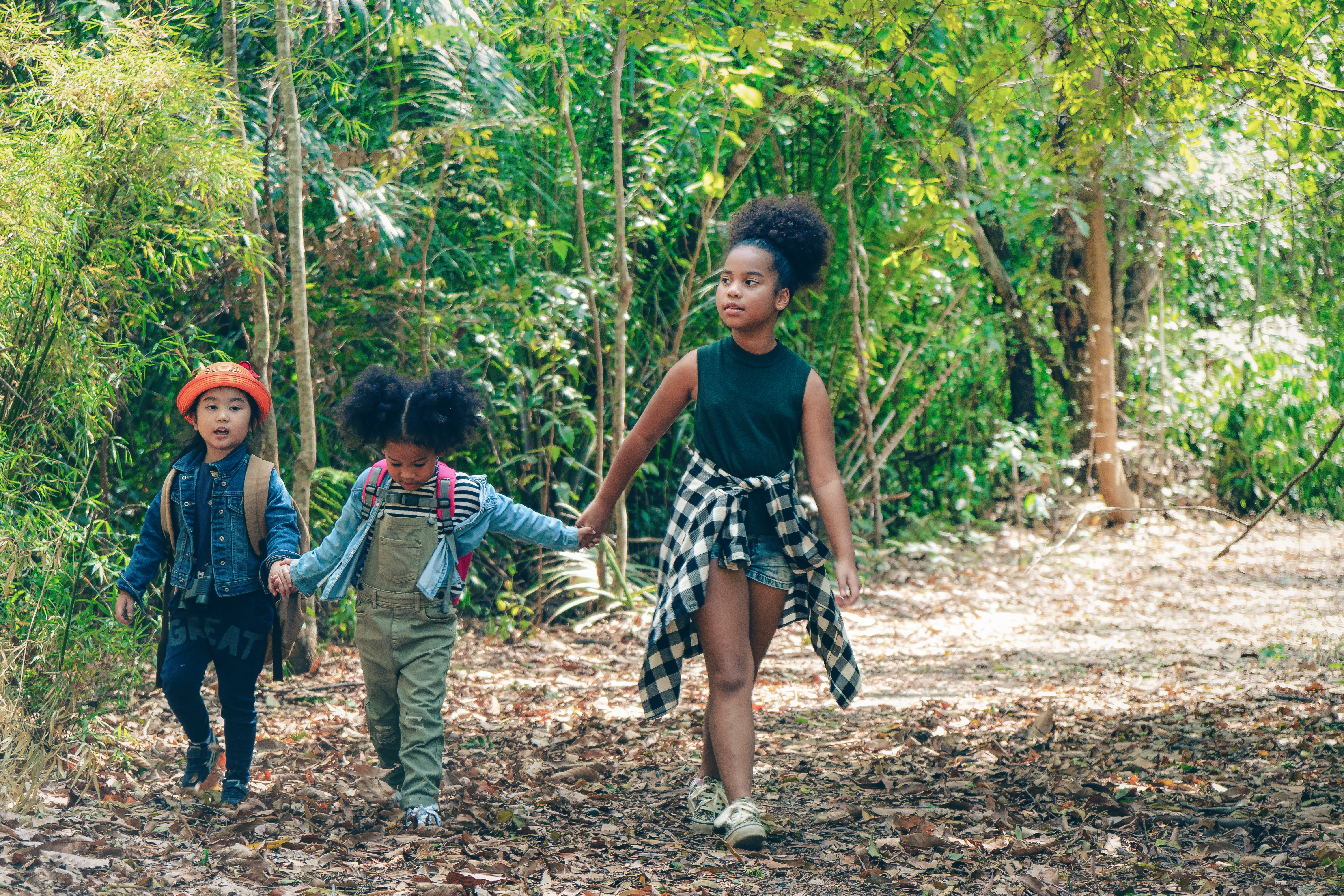 three kids playing in the woods