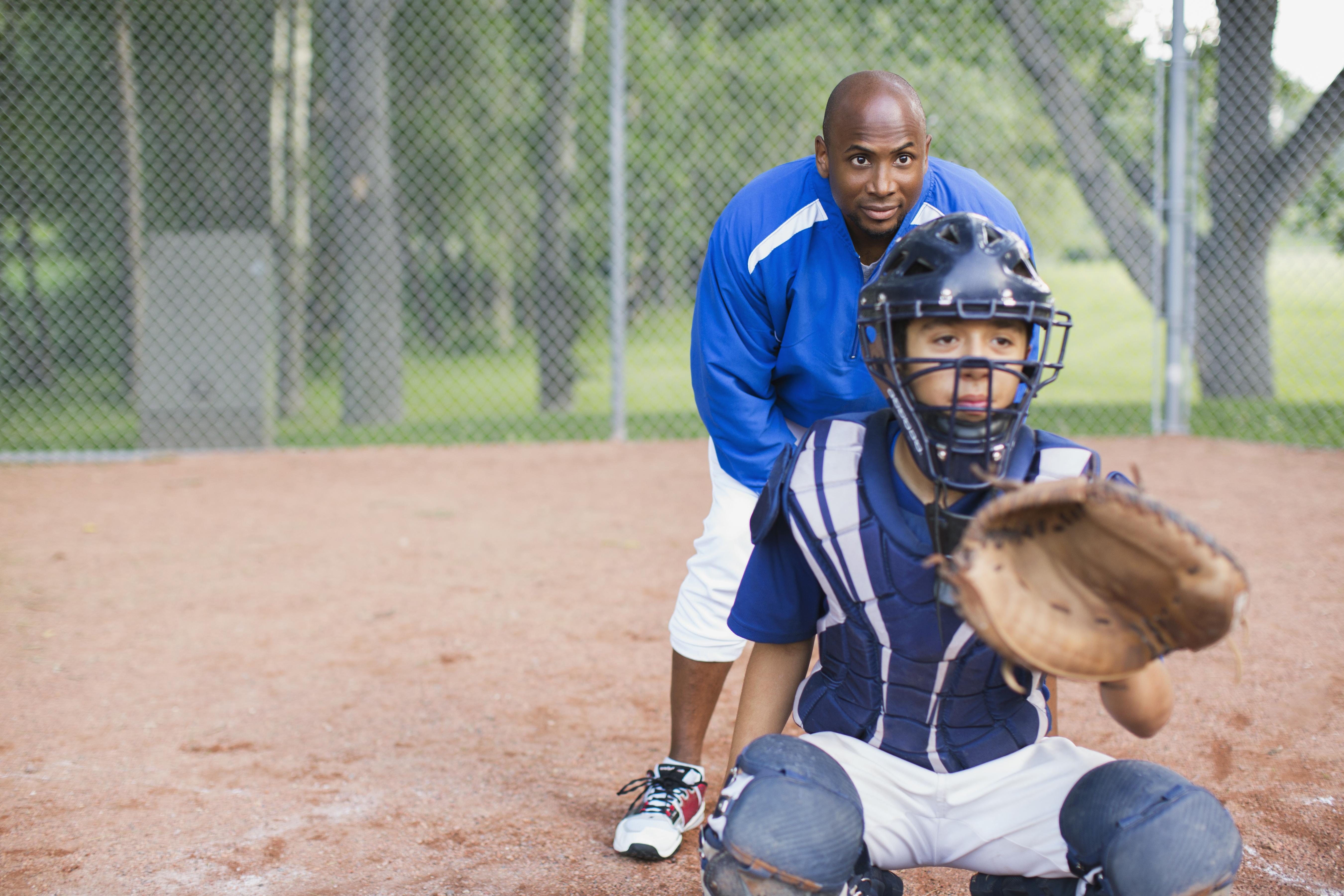 Child and coach playing baseball