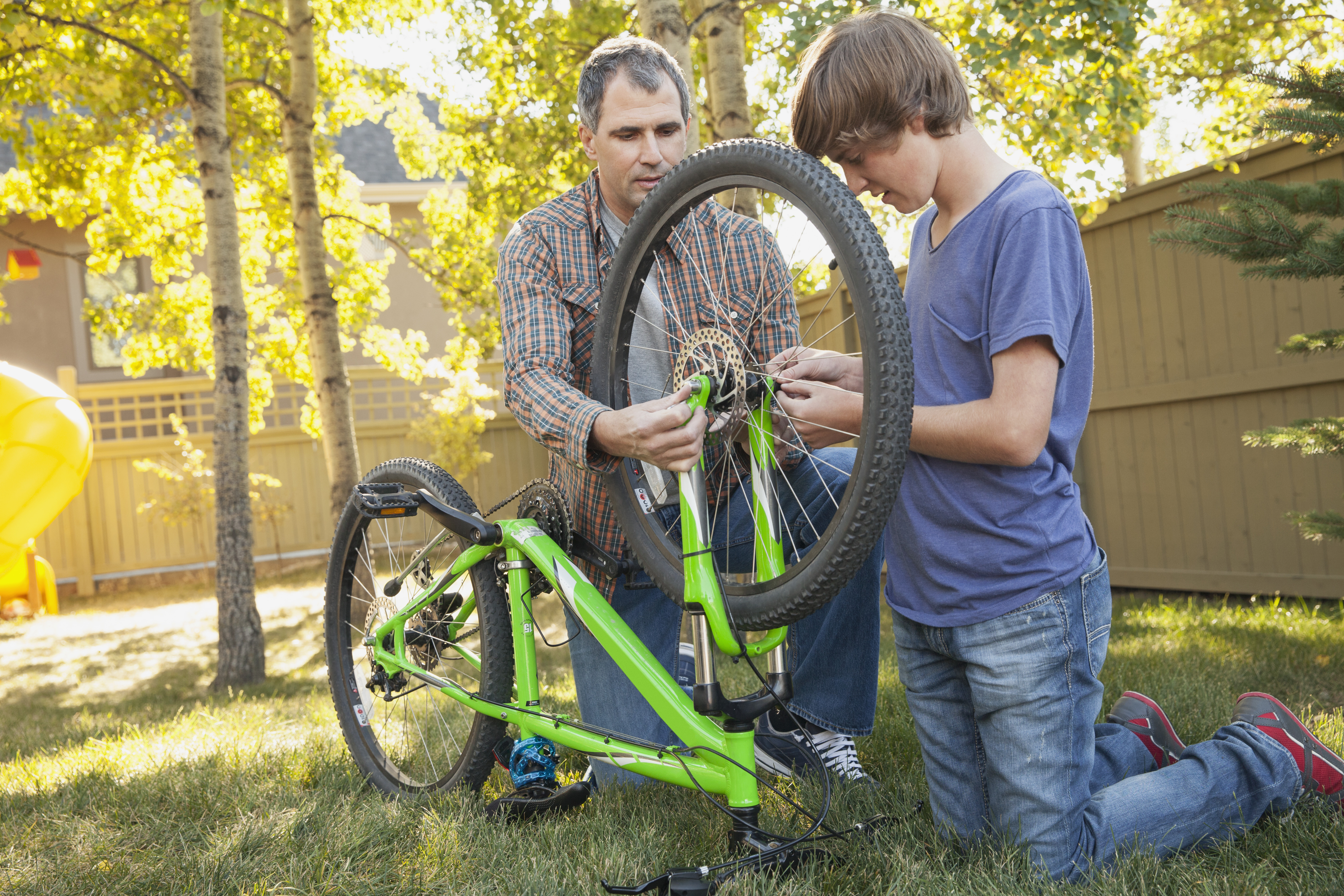 teen boy and dad working on a bike in backyard