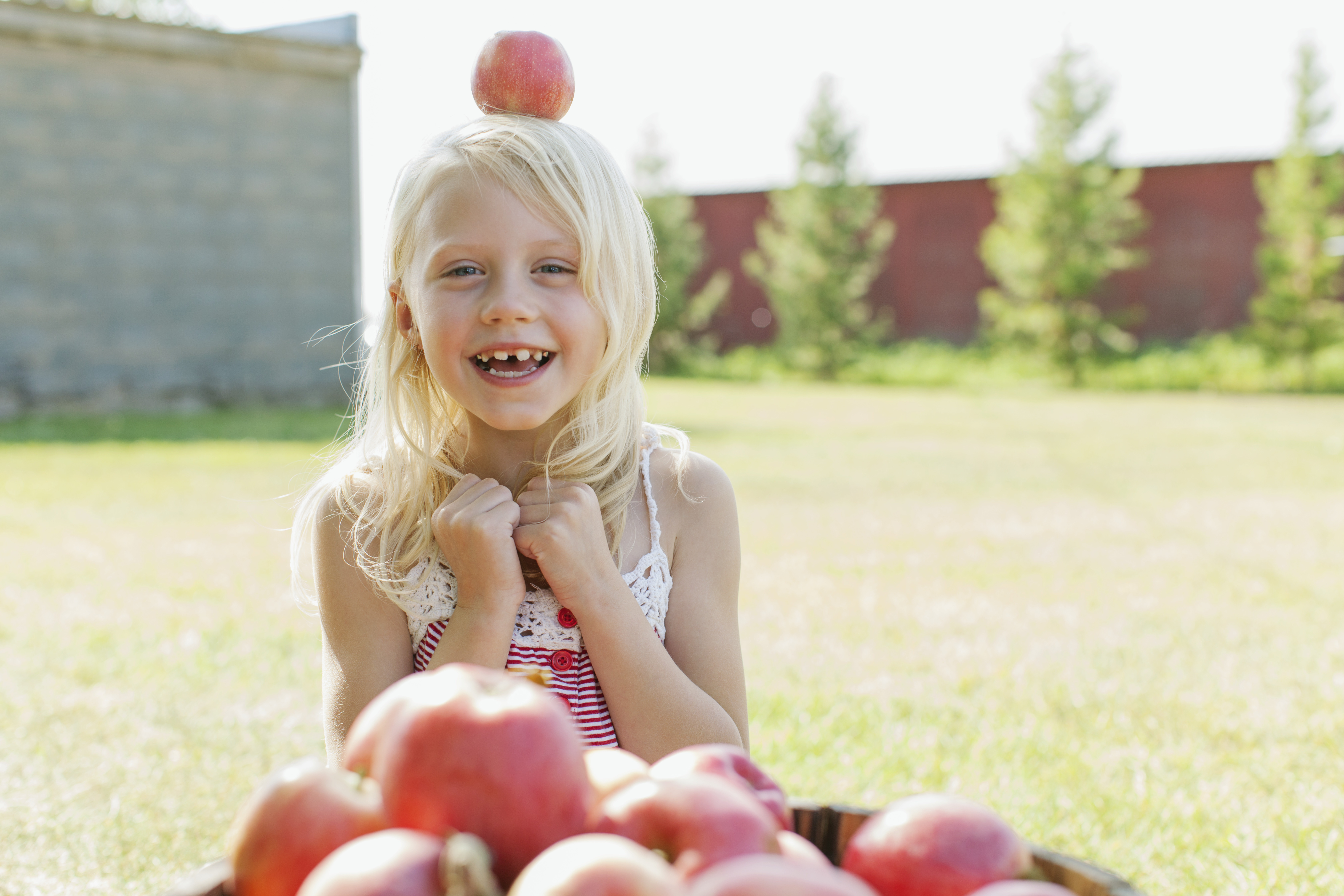 Little girl with an apple on her head