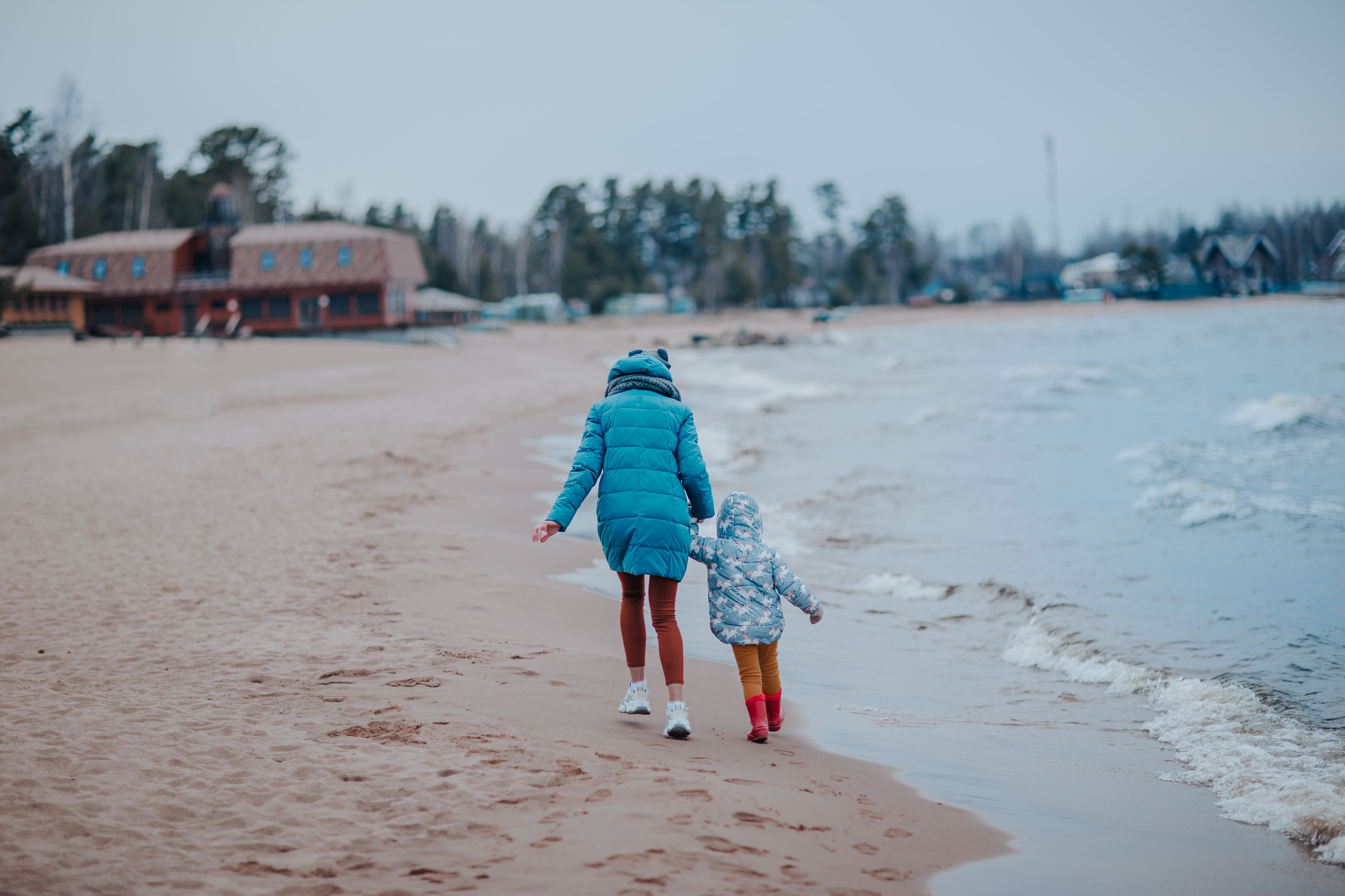 adult and child walking down a beach