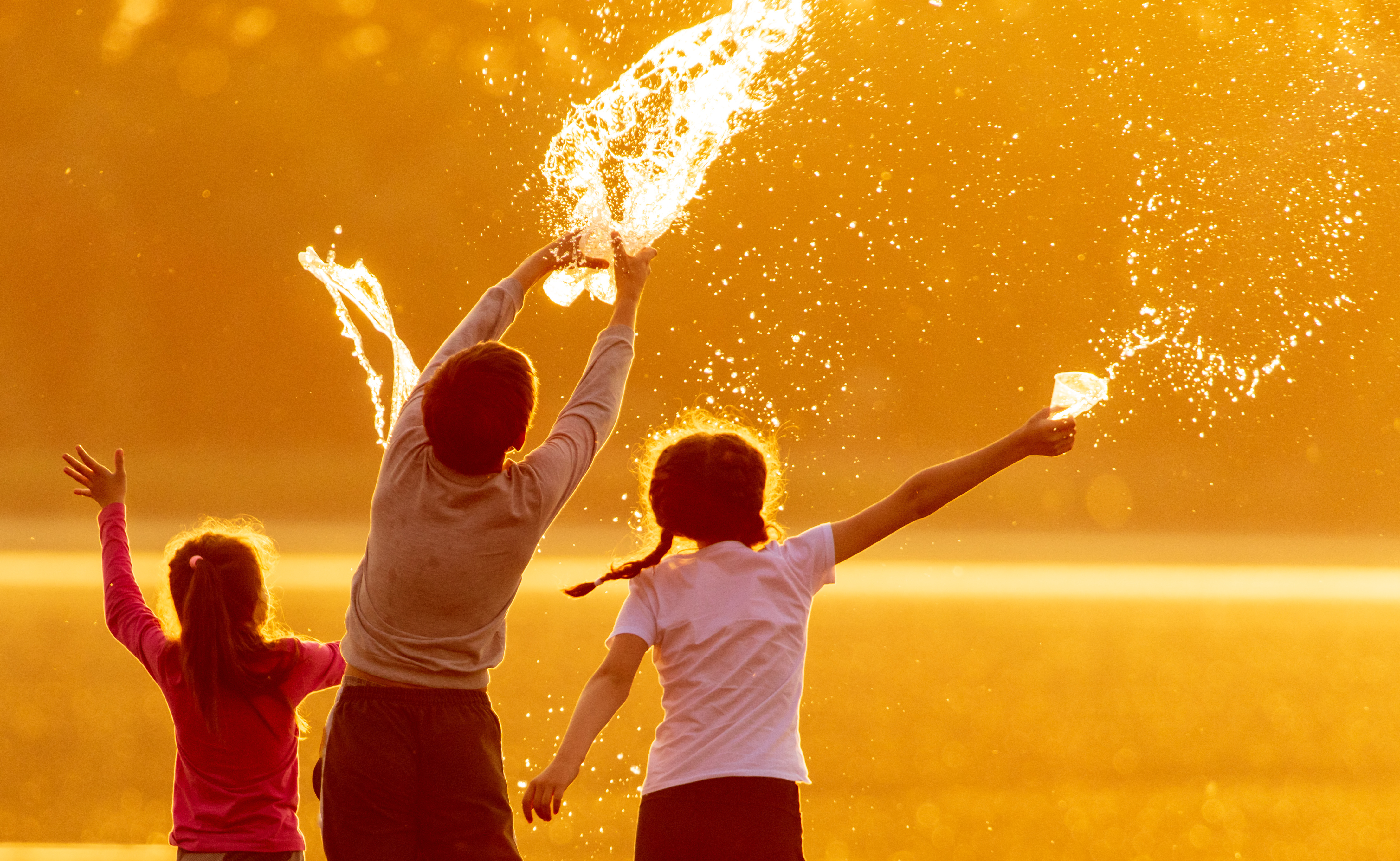 kids throw water while playing outside