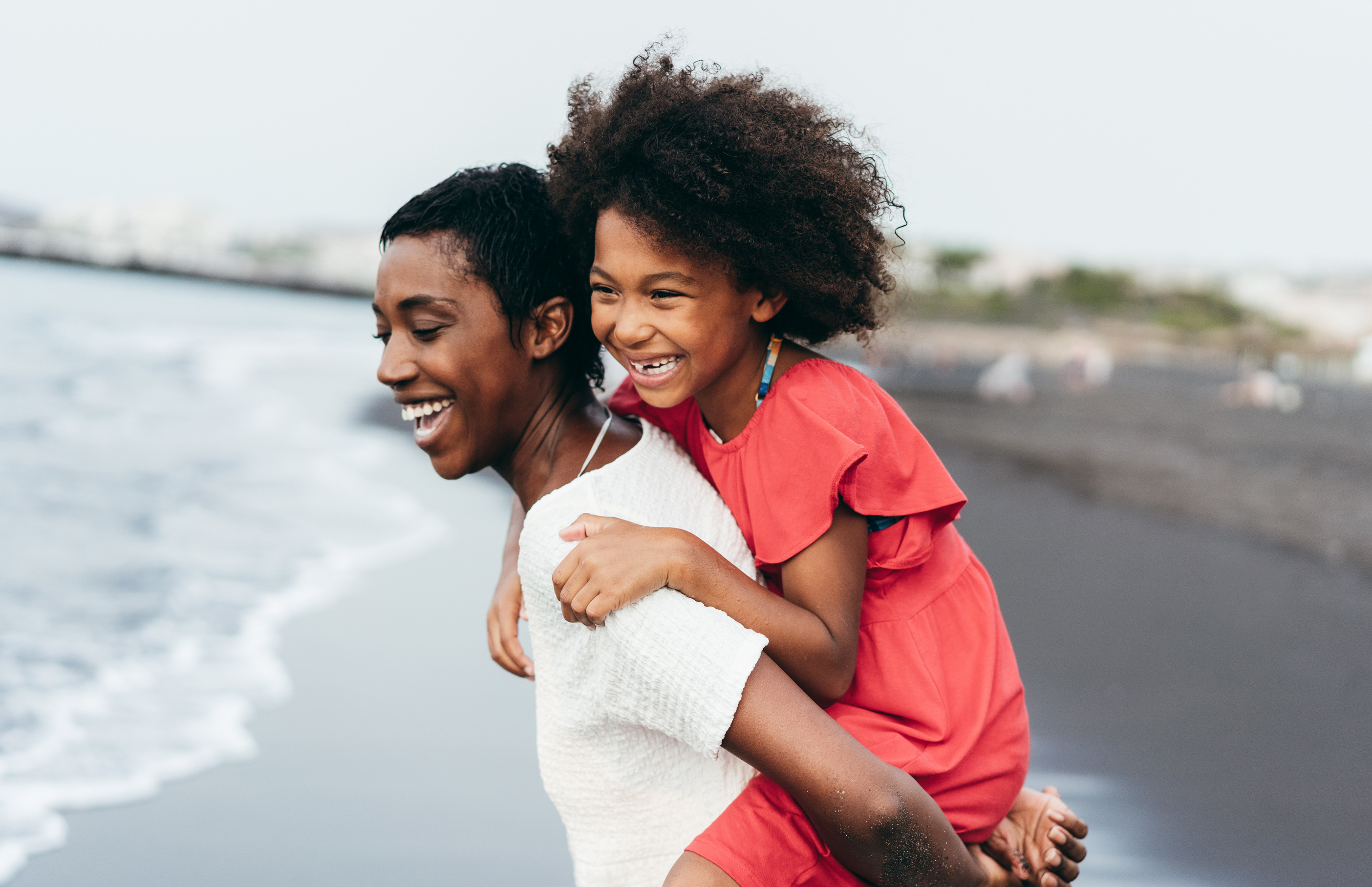 mother and daughter laughing on a beach