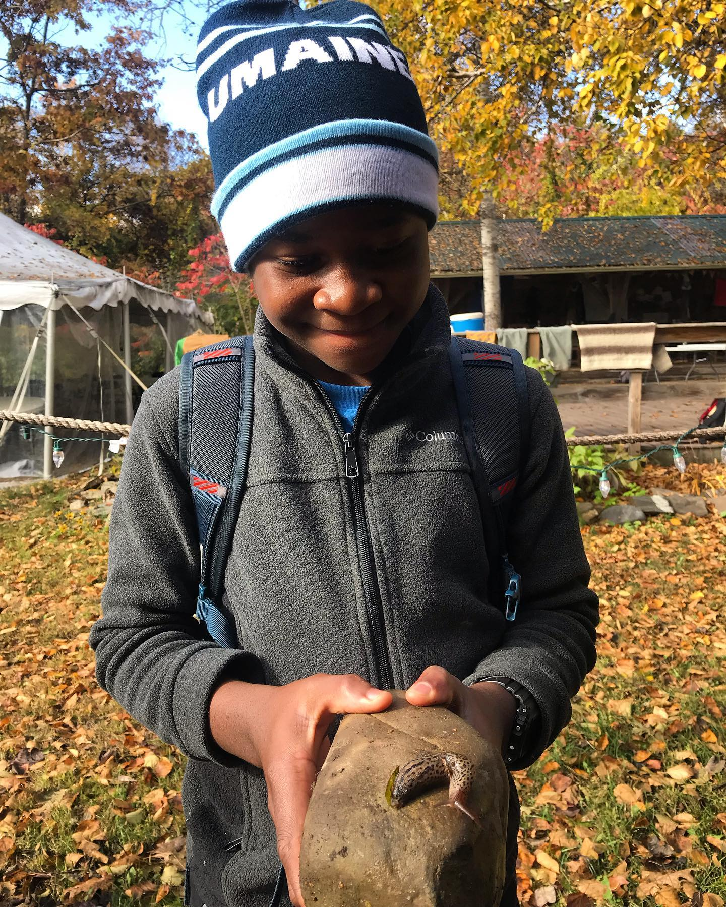 a young boy holds a rock with a slug on it